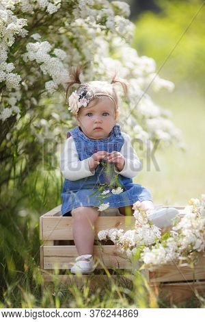 Portrait Of A Beautiful Little Girl 1 Year Old With Blue-gray Emerald Eyes In A Blooming Spring-summ
