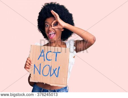 Young african american woman holding act now banner smiling happy doing ok sign with hand on eye looking through fingers