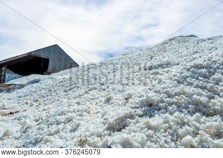 Brine Salt Farm Warehouse With Sky And Clouds. Pile Of Organic Sea Salt. Raw Material Of Salt Indust