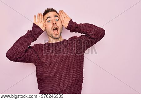 Young handsome man with blue eyes wearing casual sweater standing over pink background Smiling cheerful playing peek a boo with hands showing face. Surprised and exited