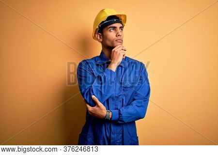 Young handsome african american worker man wearing blue uniform and security helmet with hand on chin thinking about question, pensive expression. Smiling with thoughtful face. Doubt concept.