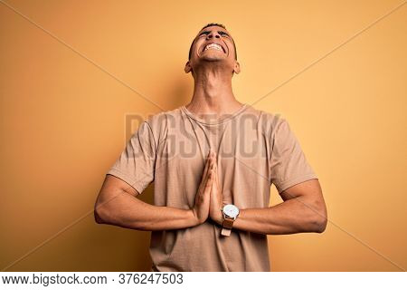 Young handsome african american man wearing casual t-shirt standing over yellow background begging and praying with hands together with hope expression on face very emotional and worried. Begging.