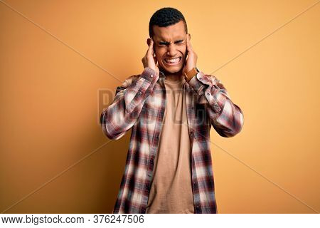 Young handsome african american man wearing casual shirt standing over yellow background covering ears with fingers with annoyed expression for the noise of loud music. Deaf concept.