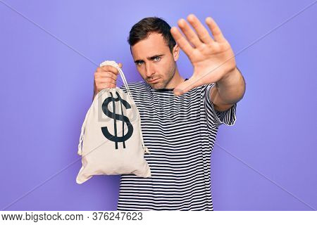 Young handsome man with blue eyes holding bag with dollar symbol over purple background with open hand doing stop sign with serious and confident expression, defense gesture