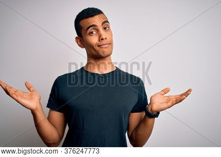 Young handsome african american man wearing casual t-shirt standing over white background clueless and confused expression with arms and hands raised. Doubt concept.
