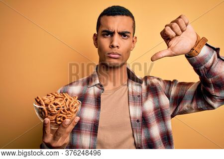 Young handsome african american man holding bowl with german baked pretzels with angry face, negative sign showing dislike with thumbs down, rejection concept