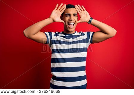 Handsome african american man wearing casual striped t-shirt standing over red background Smiling cheerful playing peek a boo with hands showing face. Surprised and exited
