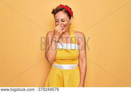 Middle age senior pin up woman wearing 50s style retro dress over yellow background smelling something stinky and disgusting, intolerable smell, holding breath with fingers on nose. Bad smell