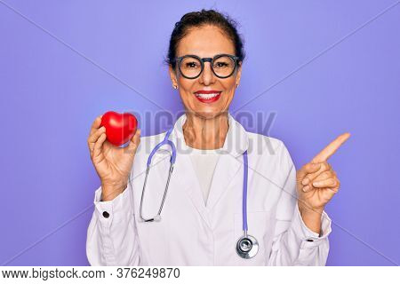 Middle age senior cardiologist doctor woman holding red heart over purple background very happy pointing with hand and finger to the side