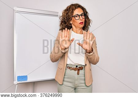 Middle age senior business woman standing on seminar presentation by magnectic blackboard Moving away hands palms showing refusal and denial with afraid and disgusting expression. Stop and forbidden.