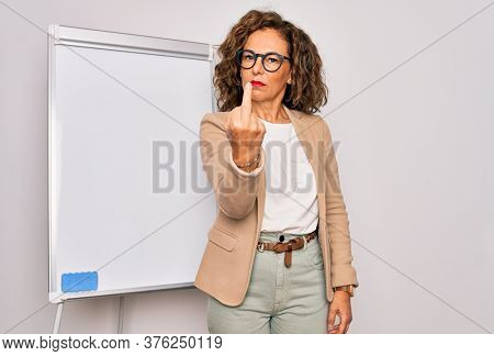 Middle age senior business woman standing on seminar presentation by magnectic blackboard Showing middle finger, impolite and rude fuck off expression