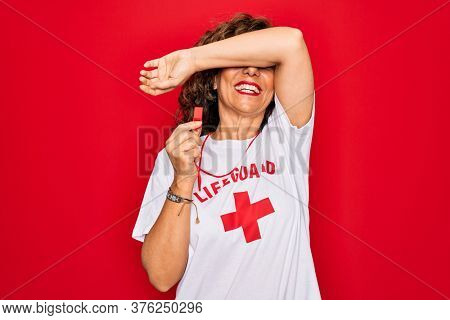Middle age senior summer lifeguard woman holding whistle over red background Smiling cheerful playing peek a boo with hands showing face. Surprised and exited