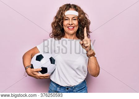Middle age beautiful sporty woman playing soccer holding football bal over pink background smiling with an idea or question pointing finger with happy face, number one