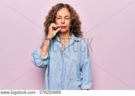Middle age beautiful woman wearing casual denim shirt standing over pink background mouth and lips shut as zip with fingers. Secret and silent, taboo talking