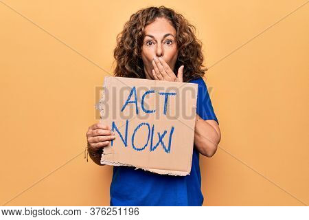 Middle age beautiful woman asking for react holding banner with act now message covering mouth with hand, shocked and afraid for mistake. Surprised expression