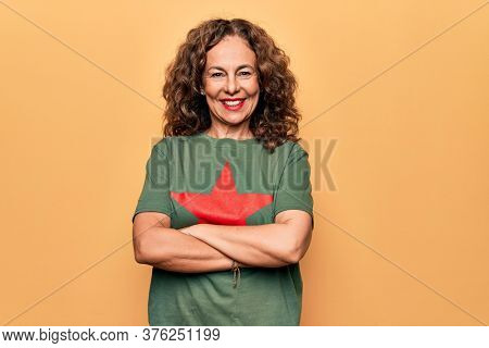 Middle age beautiful woman wearing t-shirt with red star revolutionary symbol of communism happy face smiling with crossed arms looking at the camera. Positive person.
