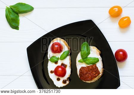 Tasty Vegetarian Bruschettas With Dried And Fresh Tomatoes In Black Plate On White Wooden Table, Top