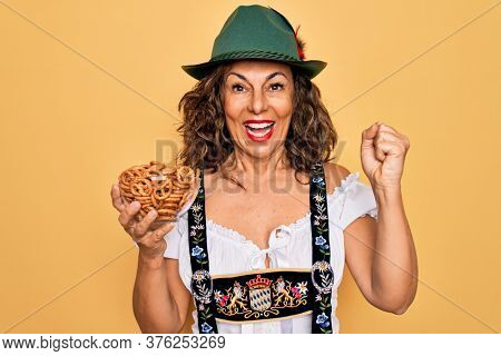 Middle age woman wearing traditional octoberfest dress holding bowl with baked pretzels screaming proud and celebrating victory and success very excited, cheering emotion