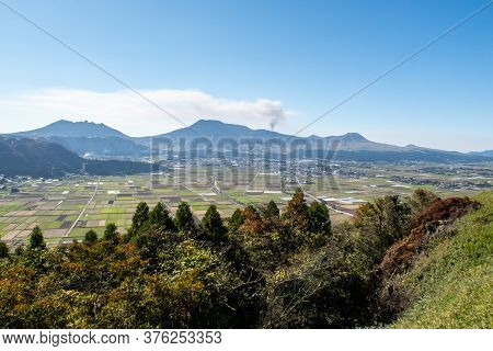 Distant View Of Aso Valley And Mountain Ridge With Mount Aso Volcano Venting Steam On Sunny Autumn D