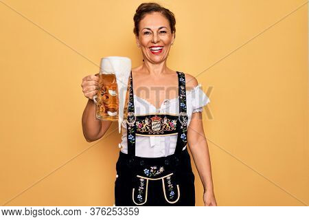 Middle age brunette woman wearing german traditional oktoberfest dress drinking jar of beer with a happy face standing and smiling with a confident smile showing teeth