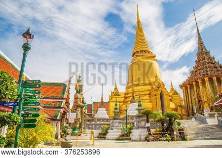 A Demon Guardian Statue With The Great Golden Stupa In Wat Phra Kaew Against The Sky, Temple Of The