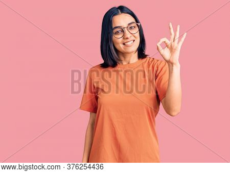 Young beautiful latin woman wearing casual clothes smiling positive doing ok sign with hand and fingers. successful expression.