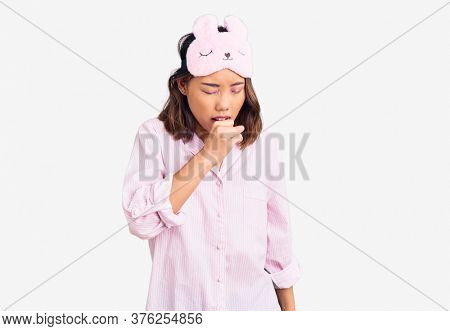 Young beautiful chinese girl wearing sleep mask and pajama feeling unwell and coughing as symptom for cold or bronchitis. health care concept.