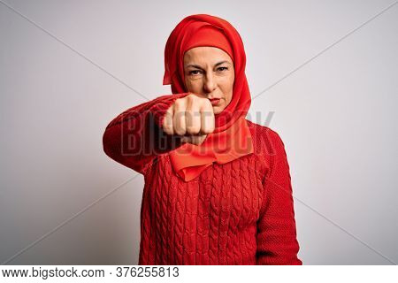 Middle age brunette woman wearing muslim traditional hijab over isolated white background Punching fist to fight, aggressive and angry attack, threat and violence