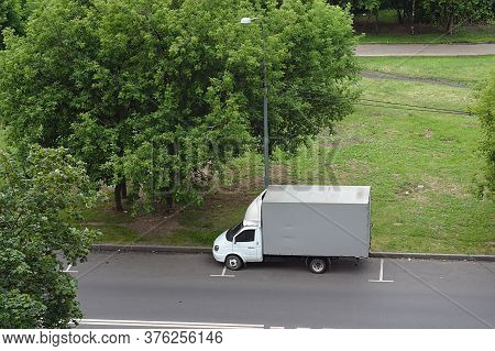 A Small Truck Is Parked On The Outskirts Of The City