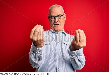Middle age handsome hoary man wearing casual striped shirt and glasses over red background doing money gesture with hands, asking for salary payment, millionaire business