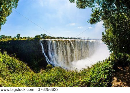 Giant cloud of water fog over Victoria Falls. Victoria National Park. The waterfall on the Zambezi River. Journey after the wet season. Concept of extreme and photo tourism