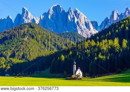 Tyrol, Italy. Small white church with a bell among green lawns on the sunset. The gorgeous village in the world, Santa Maddalena in the Val di Funes Valley. The concept of ecological and photo tourism