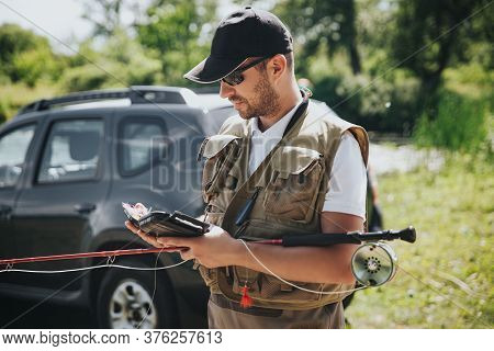 Young Fisherman Fishing On Lake Or River. Busy Guy Using Smartphone. Stand At Car And Holding Fishin