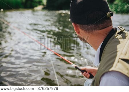 Young Fisherman Fishing On Lake Or River. Back View Of Guy Holding Fishing Rod In Hand And Looking A