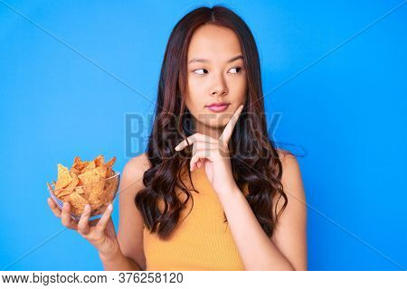 Young beautiful chinese girl holding nachos potato chips serious face thinking about question with hand on chin, thoughtful about confusing idea