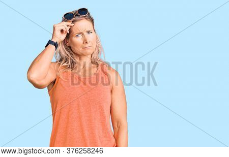 Middle age fit blonde woman wearing casual summer clothes and sunglasses worried and stressed about a problem with hand on forehead, nervous and anxious for crisis