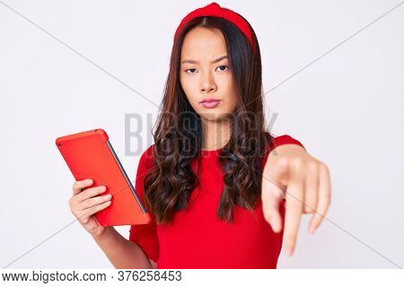 Young beautiful chinese girl holding touchpad pointing with finger to the camera and to you, confident gesture looking serious