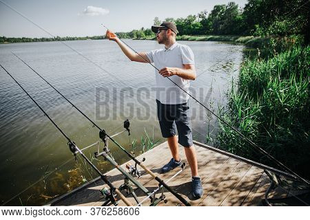 Young Fisherman Fishing On Lake Or River. Guy Has Three Rods Fishing And Trying To Find Fish In Wate
