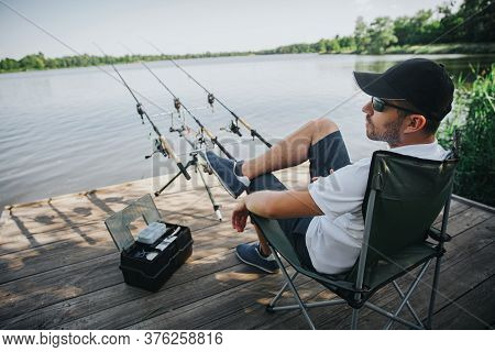 Young Fisherman Fishing On Lake Or River. Side View Of Adult Guy Sitting In Folding Chair Alone At R