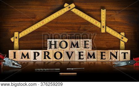 Yellow Wooden Folding Ruler In The Shape Of A House And The Text Home Improvement, Made Of Wooden Bl