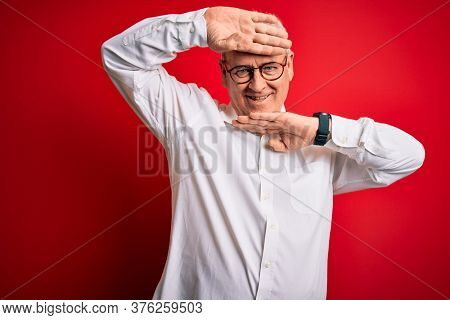 Middle age handsome hoary man wearing casual shirt and glasses over red background Smiling cheerful playing peek a boo with hands showing face. Surprised and exited