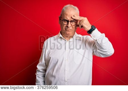 Middle age handsome hoary man wearing casual shirt and glasses over red background worried and stressed about a problem with hand on forehead, nervous and anxious for crisis