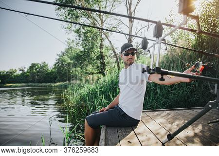 Young Fisherman Fishing On Lake Or River. Guy Sit Alone At Water Pier And Look Back On Fish-rods. Ad