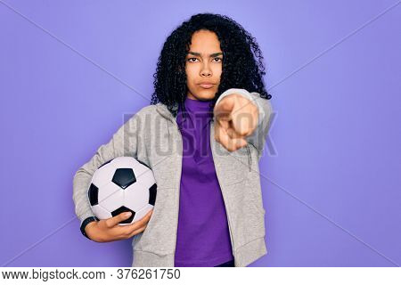 African american curly player woman playing soccer holding football bal over purple background pointing with finger to the camera and to you, hand sign, positive and confident gesture from the front