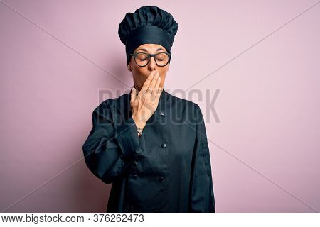 Middle age brunette chef woman wearing cooker uniform and hat over isolated pink background bored yawning tired covering mouth with hand. Restless and sleepiness.