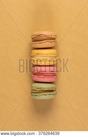 Four Delicious Colorful Macaroonson Yellow Vinyl Background.