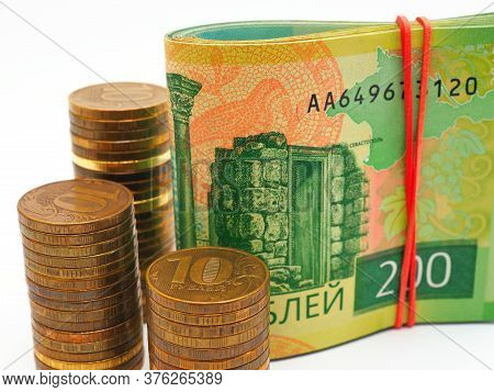 Piles Of Russian Coins Of 10 Rubles Stand Next To A Bundle Of Notes Of 200 Rubles. Contrast And Satu