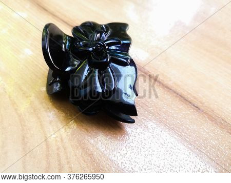 A Black Hair Clip Claw Type Placed Isolated In A Floor.the Clip Has A Good Decoration And A Shining