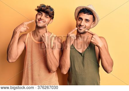 Young gay couple wearing summer clothes smiling cheerful showing and pointing with fingers teeth and mouth. dental health concept.