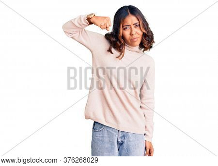 Young beautiful mixed race woman wearing winter turtleneck sweater strong person showing arm muscle, confident and proud of power
